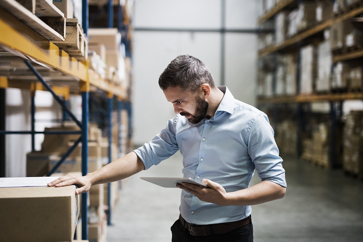 Man in warehouse examining box with tablet in hand